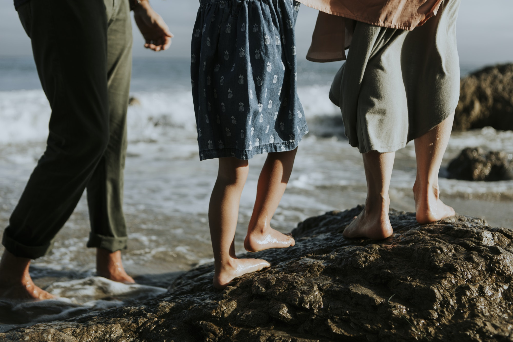 A shot of people's feet walking on rocks at the beach