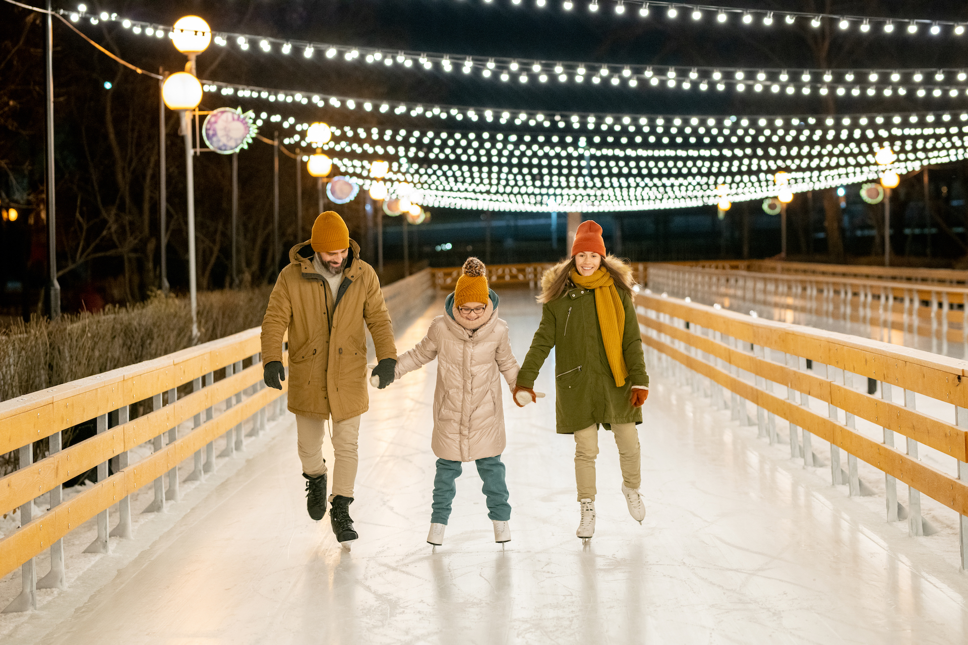 Two parents teaching their daughter to skate they holding hands and skating on rink outdoors
